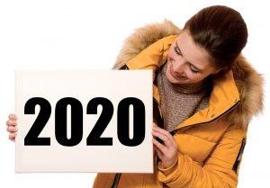 eine junge frau haelt ein schild mit der aufschrift 2020 in der hand