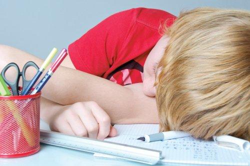 Kind mit ADHS sitzt an Schreibtisch