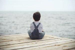 Trauriges Kind guckt auf Meer