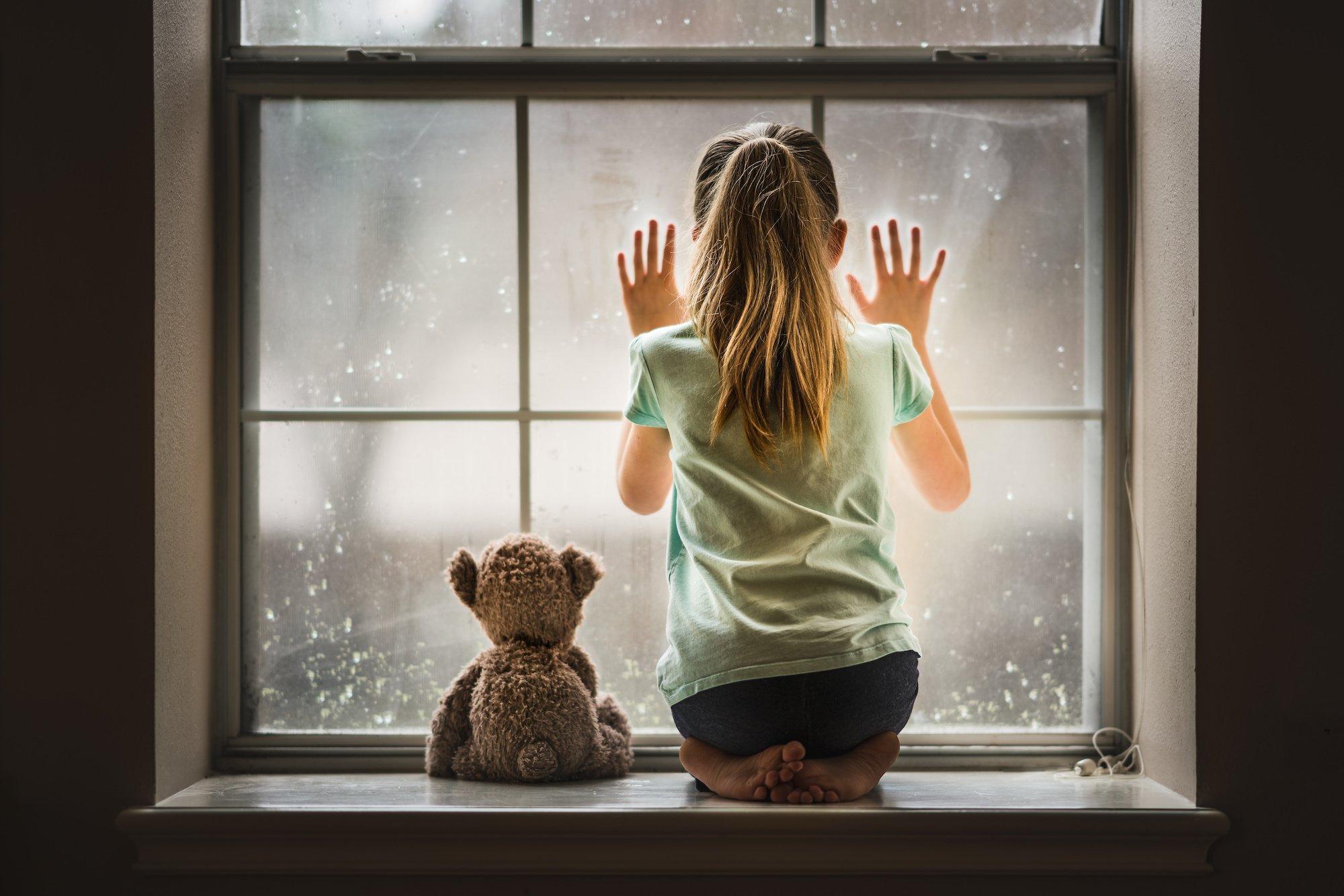 Mädchen mit Heimweh guckt aus dem Fenster mit Bär