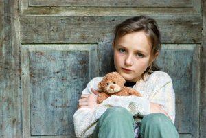 Kind mit Heimweh hält Kuscheltier