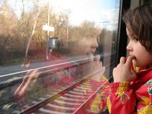 Kind mit Heimweh guckt aus dem Fenster
