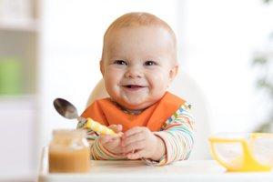 lachendes Baby hält Löffel