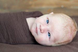 blauaeugiges Baby schielt in die Kamera