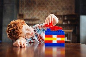 Kind baut einen Turn aus Legosteinen