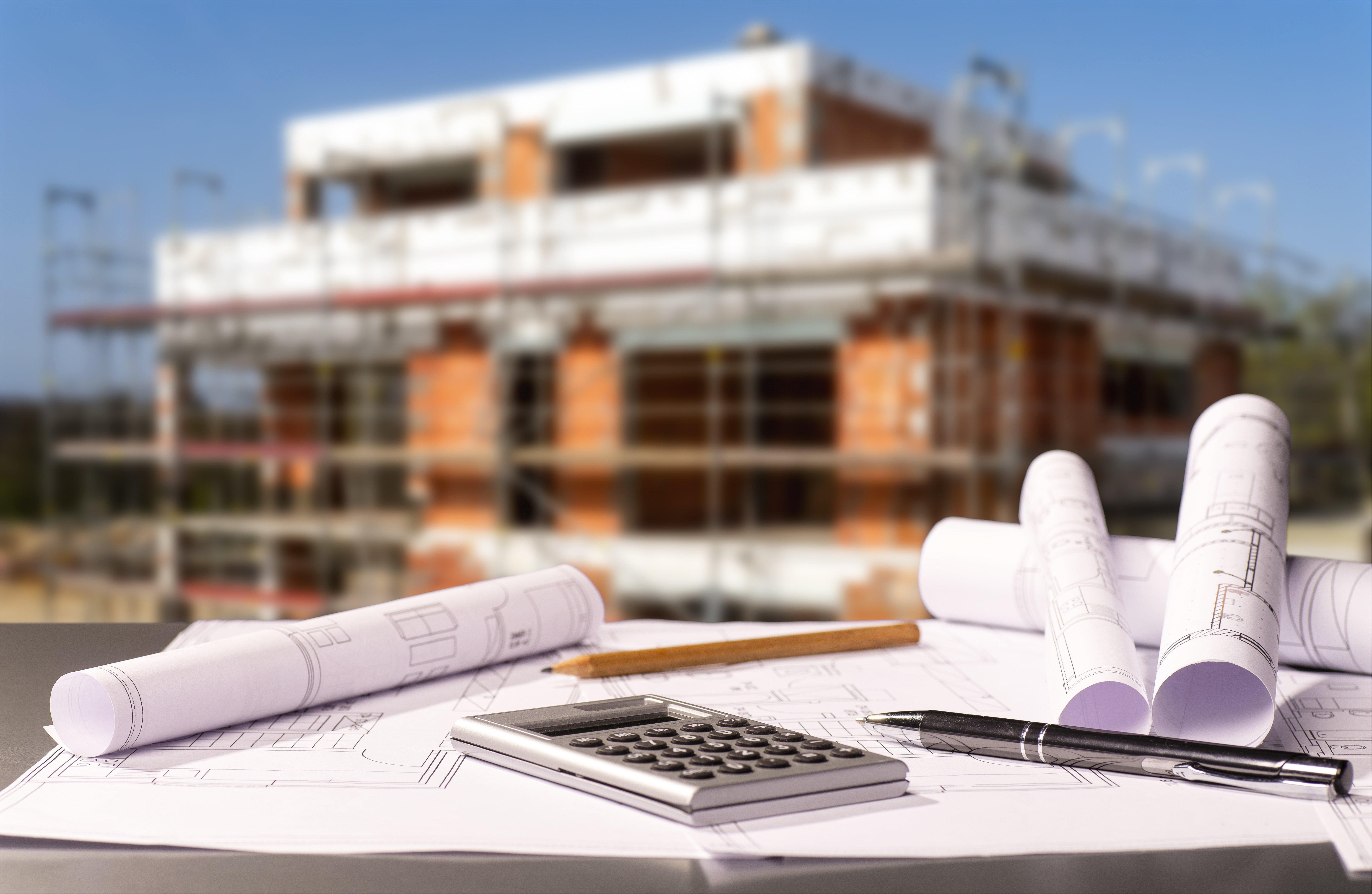 Baupläne mit Taschenrechner und einem Rohbau im Hintergrund