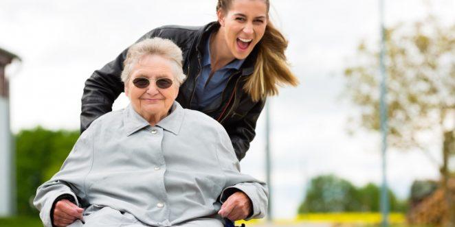 Frau mit Großmutter im Rollstuhl