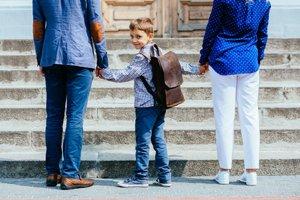 Eltern halten Kind an den Händen