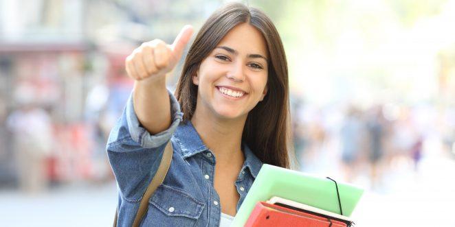 Glückliche Studentin zeigt Daumen hoch