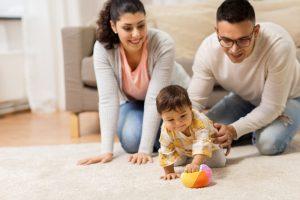 Eltern schauen Kind beim Krabbeln zu