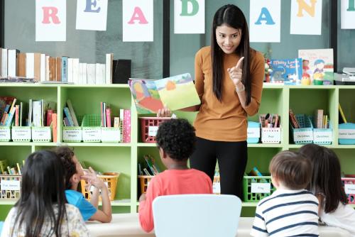Erzieherin zeigt Kindern ein Buch