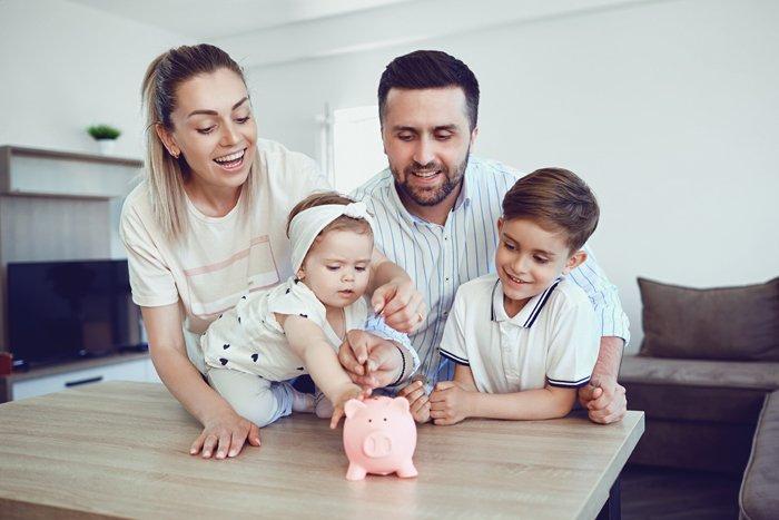Eltern und zwei kleine Kinder fuettern Sparschwein
