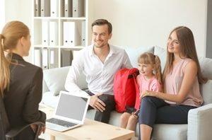 Eltern und Kind sitzen bei Direktorin