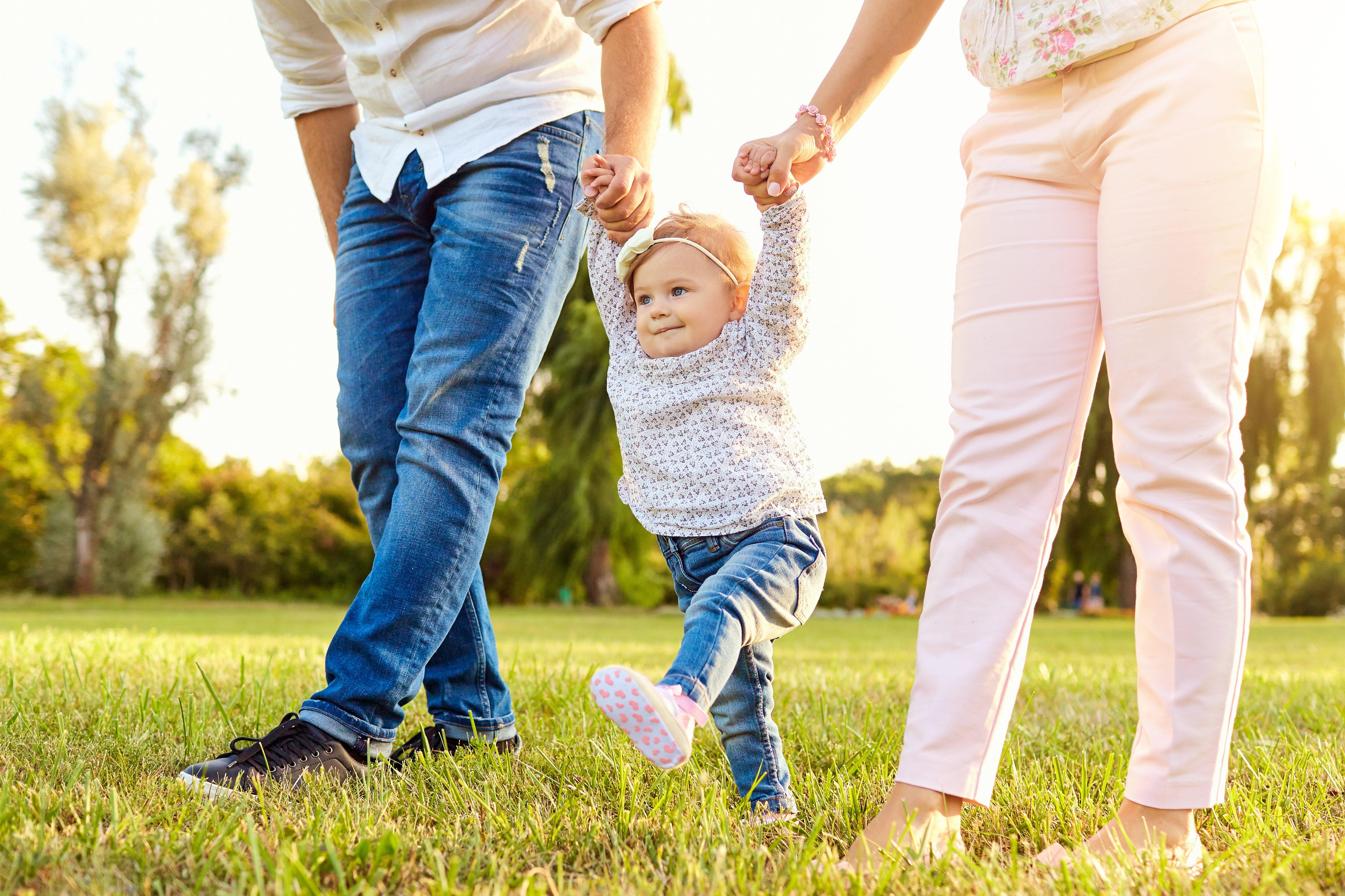 Eltern halten Baby an den Händen