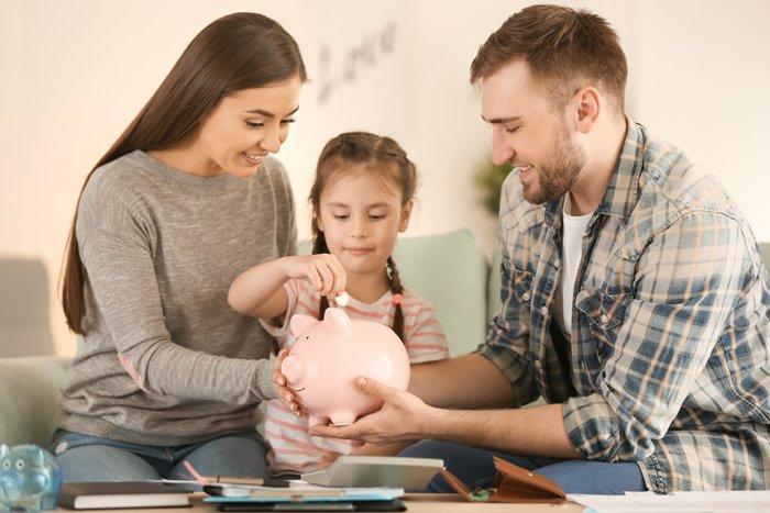 Eltern auf Sofa, Kind dazwischen füttert Sparschwein
