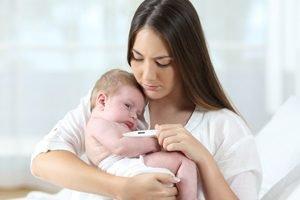 Frau misst Fieber bei ihrem Baby