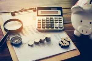 Bürobedarf, Sparschwein und Kleingeld auf einem Tisch