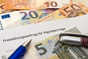 Geldscheine und Formular für Freistellungsauftrag