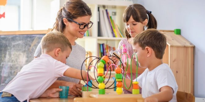 Erzieherin schaut Kindern beim Spielen zu
