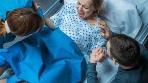 Frau schreit bei der Geburt, Mann und Arzt kümmern sich