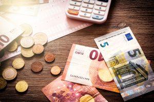 Geld in Münzen und Scheinen sowie Taschenrechner