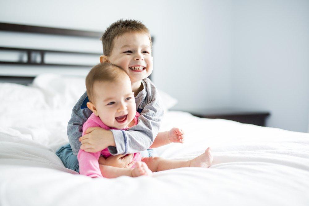 Geschwister spielen auf Bett