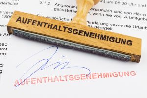 Ein Stempel aus Holz liegt auf einem Dokument. Deutsche Aufschrift Aufenthaltsgenehmigung: