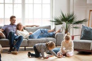 junge Eltern auf dem Sofa, Kinder spielen auf dem Boden