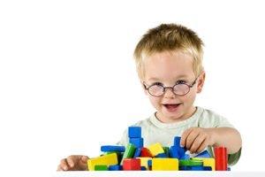 Junge mit Brille spielt mit Baukloetzen