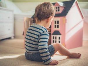 Junge spielt mit Puppenhaus
