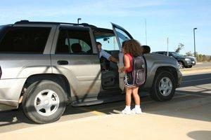 kleines Maedchen steht vor einer offenen Autotuer