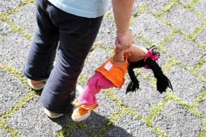 Waisenkind mit Puppe