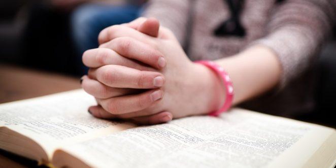 Kind betet über einem Buch