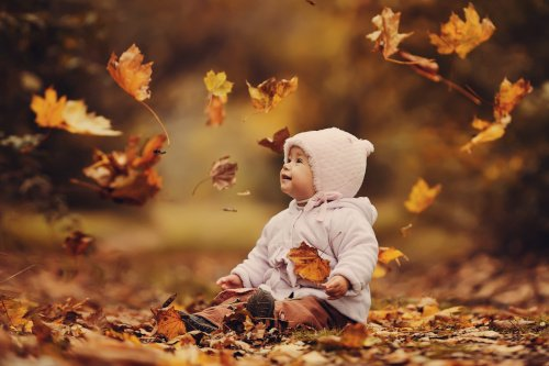 Kind in Herbstblättern