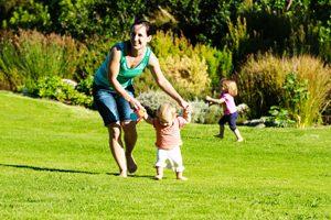 Kind lernt an den Händen der Mutter das Laufen