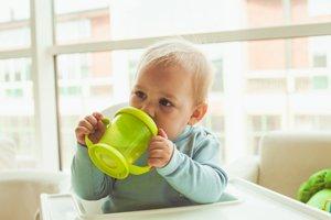 Kind im Hochstühlchen trinkt aus Schnabeltasse