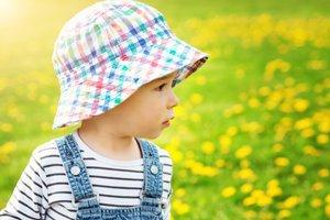 Kind mit Hut auf einer Wiese