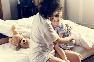 Mama neben Kind im Bett nach Alptraum