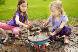 zwei Mädchen spielen im Matsch