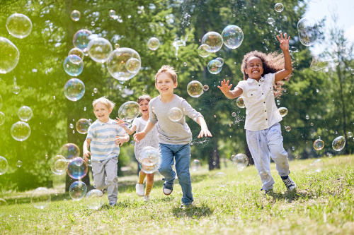 Kinder laufen Seifenblasen hinterher