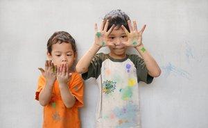zwei Jungs zeigen Flecken auf Händen und Kleidern nach dem Malen