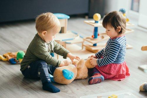 Kinder spielen auf dem Boden mit Spielzeug