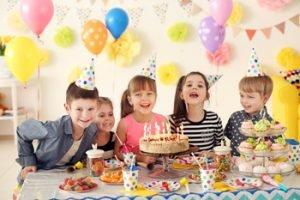 Kinder an einem dekorierten Tisch mit Torte