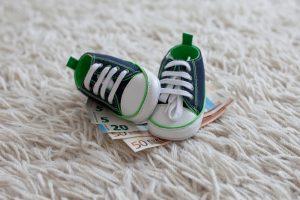 Kinderschuhe auf Geldscheinen