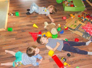 Kinder liegen in chaotischem Kinderzimmer auf dem Boden