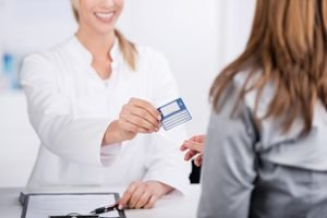 Arzthelferin gibt Patientin Krankenkassenkarte