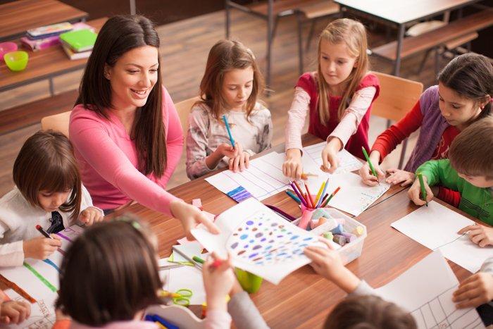 junge Lehrererin mit Kindern am Tisch