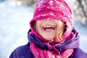 lachendes Mädchen mit rosa Mütze über den Augen im Schnee