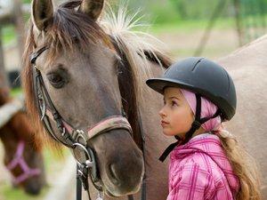 Mädchen mit Reiterkappe schaut ihr Pferd an