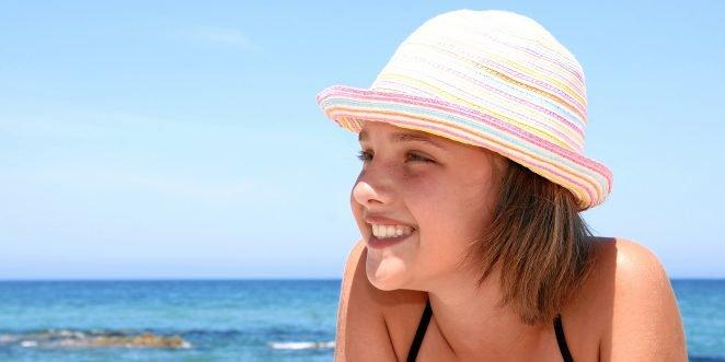 mädchen am strand mit mütze.